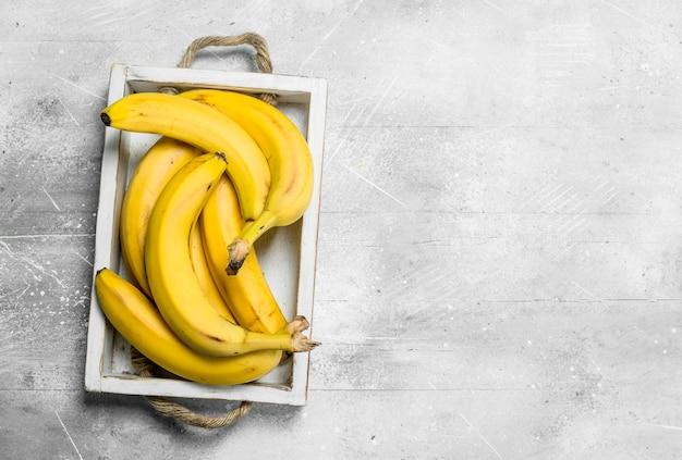 Frische bananen in einer holzkiste. auf weißem rustikalem hintergrund.