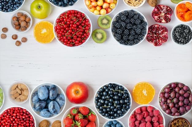 Frische beeren, früchte, nüsse auf einem weißen hölzernen hintergrund. das konzept der gesunden ernährung. lebensmittel enthalten vitamine und spurenelemente. speicherplatz kopieren.