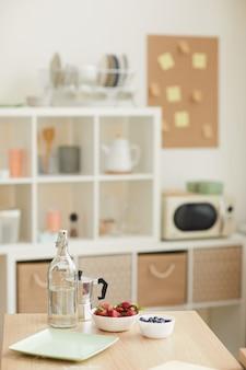 Frische beeren in schalen mit glas wasser auf dem tisch in der küche