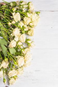 Frische beige rosen auf alten weißen holzbrettern. das festliche konzept für hochzeiten, geburtstage, 8. märz, mutter- oder valentinstag. grußkarte