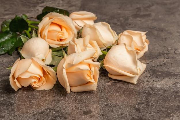 Frische beige rosen auf strukturiertem steinbetonhintergrund. das festliche konzept für hochzeiten, geburtstage, 8. märz, mutter- oder valentinstag