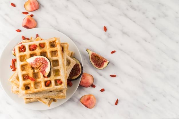 Frische belgische waffeln; und feige auf teller zum frühstück serviert