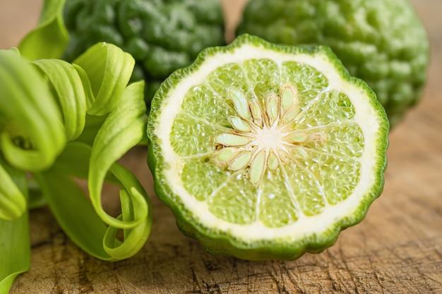 Frische bergamotte-frucht mit halbierung auf holzhintergrund.