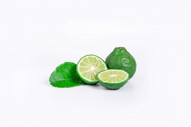 Frische bergamottenfrucht mit schnitt zur hälfte und grünes blatt lokalisiert