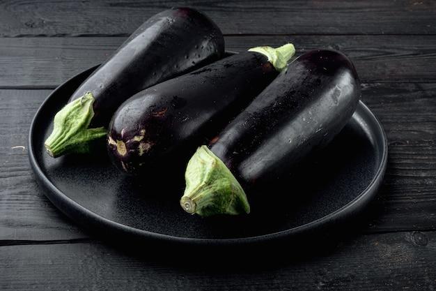 Frische bio-aubergine auf schwarzem holztisch