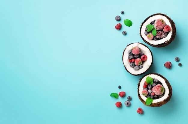 Frische bio-beeren, minze in reifen kokosnüssen. ansicht von oben. pop-art-design, kreatives sommerkonzept. die hälfte der kokosnuss in minimal flachem lay-style.
