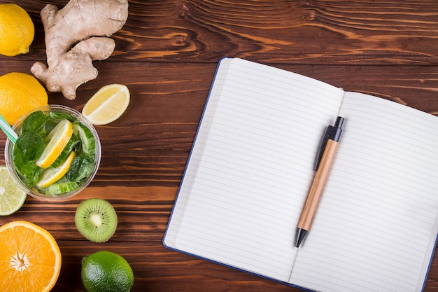 Frische bio-früchte und offenes leeres notizbuch und stift auf hölzernem hintergrund. gesundes essen und gesundes lebenskonzept. draufsicht