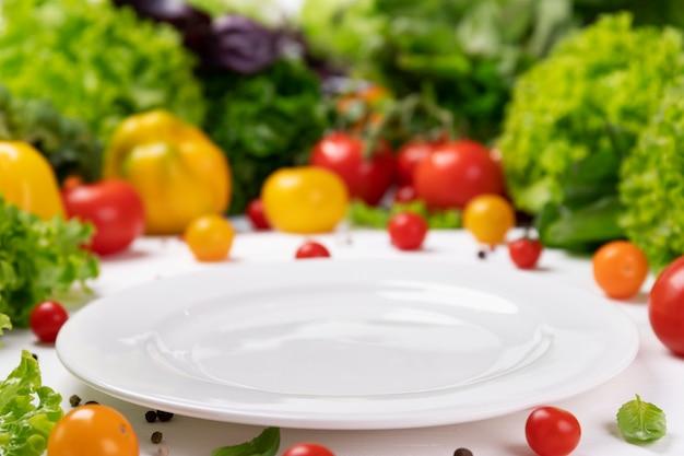 Frische bio-gemüse-zutaten für leckeres vegetarisches kochen um leere weiße platte. gesundes oder diät-lebensmittelkonzept