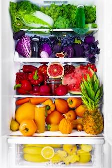 Frische bio gesunde rohe antioxidantien violett, rot, grün, orange und gelb lebensmittel, gemüse, obst und säfte in veganen vegetarischen geöffnet vollen kühlschrank mit vitaminen. gesunde ernährung und lebensstil.