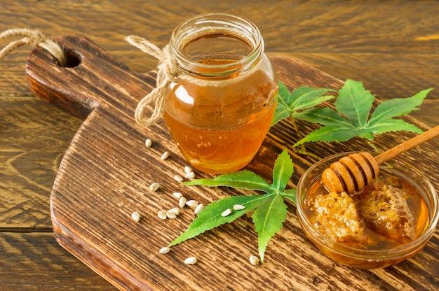 Frische bio-honew mit tieferen und cannabisblättern und -samen auf holztisch. gesunde ernährung alternative medizin.
