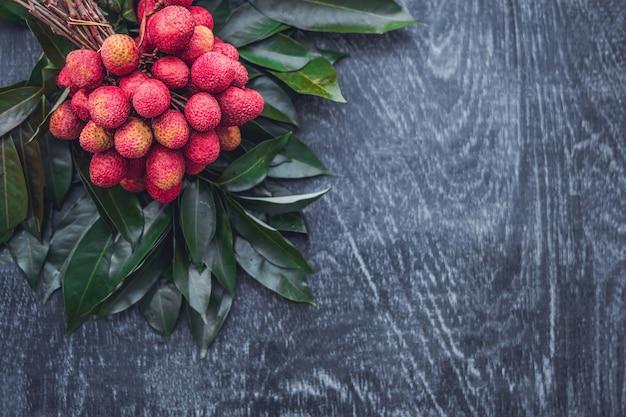 Frische bio-litschifrucht und litschiblätter auf einer rustikalen holzoberfläche