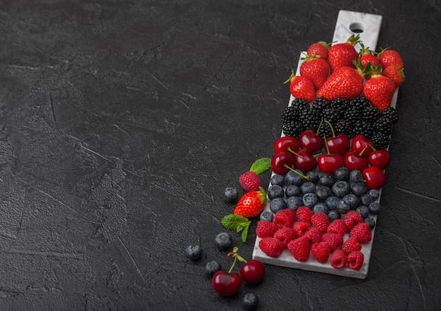 Frische bio-sommerbeeren mischen auf weißem marmorbrett auf dunklem küchentischhintergrund. himbeeren, erdbeeren, blaubeeren, brombeeren und kirschen. ansicht von oben