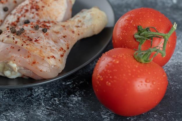 Frische bio-tomaten mit hähnchenkeulen.