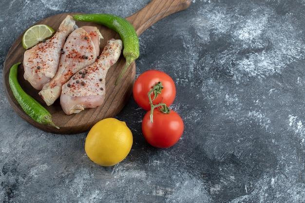Frische bio-tomaten, pfeffer und zitrone mit rohen hähnchenschenkeln.