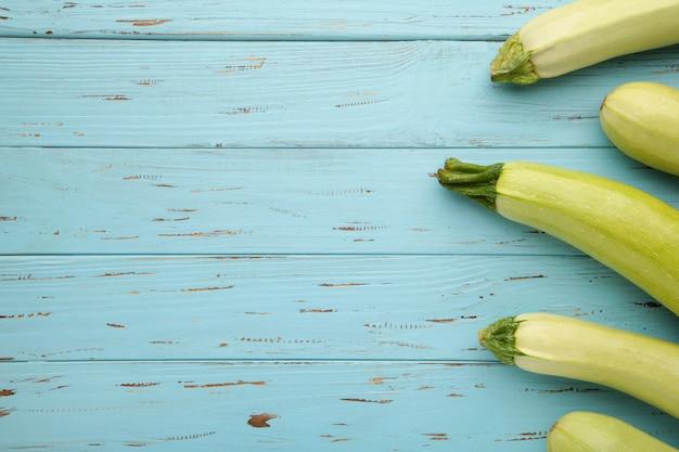 Frische bio-zucchini auf dem blauen holztisch. frischer kürbis mit kopierraum