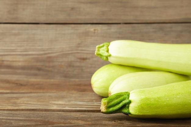 Frische bio-zucchini auf dem grauen holztisch. frischer kürbis mit kopierraum