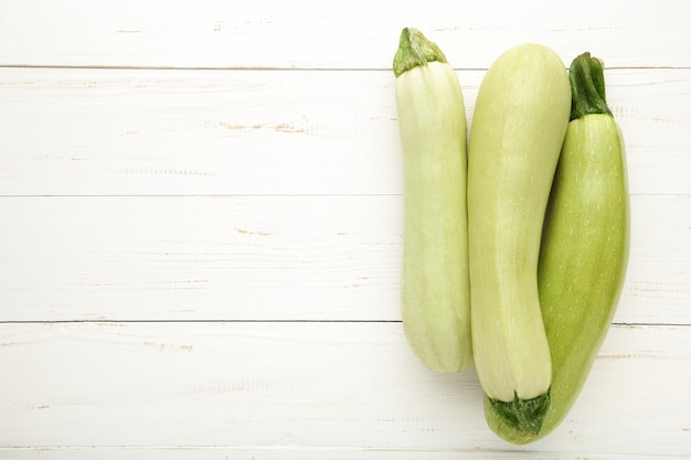Frische bio-zucchini auf dem weißen holztisch. frischer kürbis mit kopierraum