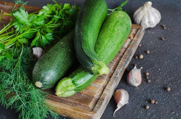 Frische bio-zucchini, knoblauch und petersilie, kräuter und gewürze.