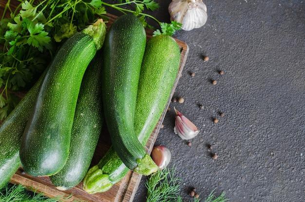 Frische bio-zucchini, knoblauch und petersilie, kräuter und gewürze