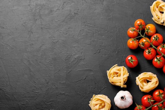 Frische bio-zutaten aus italienischen rezepten. nudeln, tomaten, knoblauch. gesundes lebensmittelkonzept.