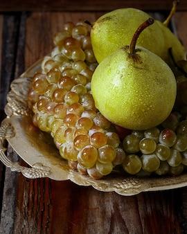 Frische birnen und grüne trauben. herbst natur konzept.