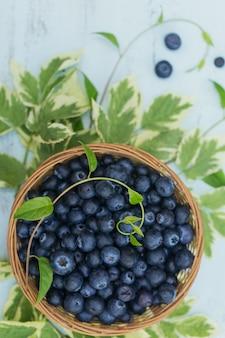 Frische blaubeeren im korb mit der draufsicht des blattmusters. gesundes essen auf weißem tischmodell