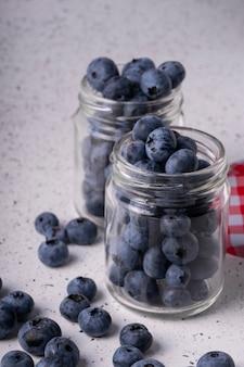 Frische blaubeeren in einem glas mit einem deckel auf grauem marmor