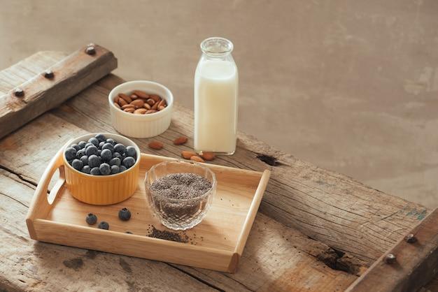 Frische blaubeeren, mandel- und chiasamen mit milch auf holzbrett. ideales gesundes frühstückskonzept.