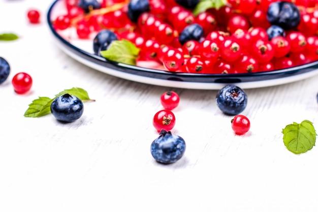 Frische blaubeeren und rote johannisbeeren mit tadellosen blättern in einer hölzernen schüssel auf leinwand. diätfutter, vegane beeren