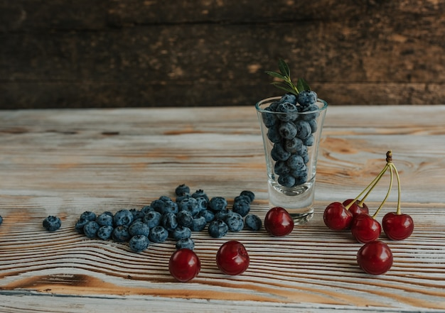 Frische blaue matte runde blaubeeren, gefüllt mit einem transparenten glas, stehen auf einem braunen, schäbig strukturierten holztisch, und überall sind beeren verstreut. daneben stehen rote saftige kirschen mit schwänzen.
