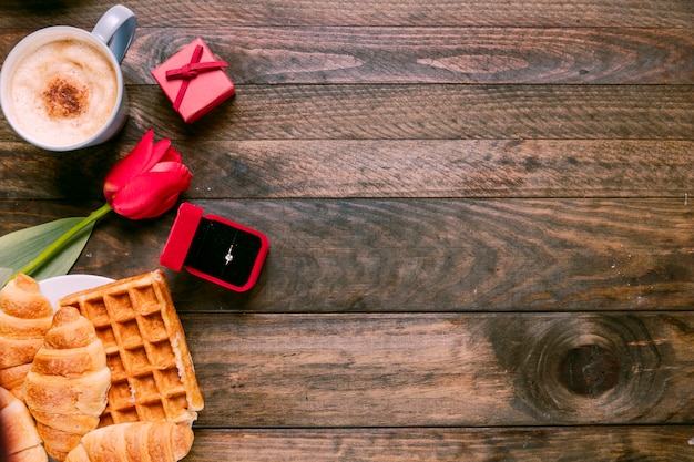 Frische blume, bäckerei, ring in geschenkbox und tasse getränk