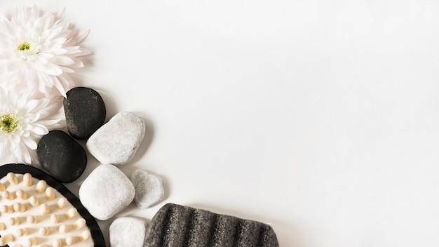 Frische blume; kieselsteine; bimsstein und massagebürste auf weißem hintergrund mit platz für text