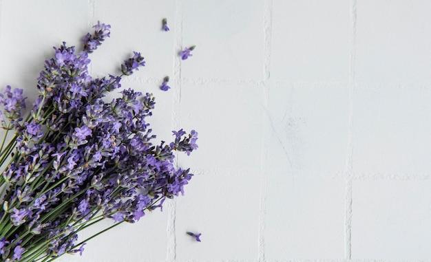 Frische blumen des lavendelblumenstraußes, draufsicht auf weißem fliesenhintergrund