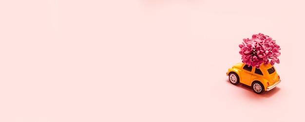 Frische blumen lieferung für den urlaub. gelbes auto des spielzeugs mit lila blumenniederlassung.