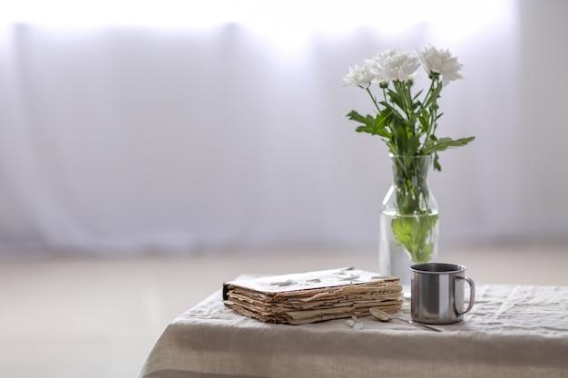 Frische blumen mit altem buch und becher auf tisch