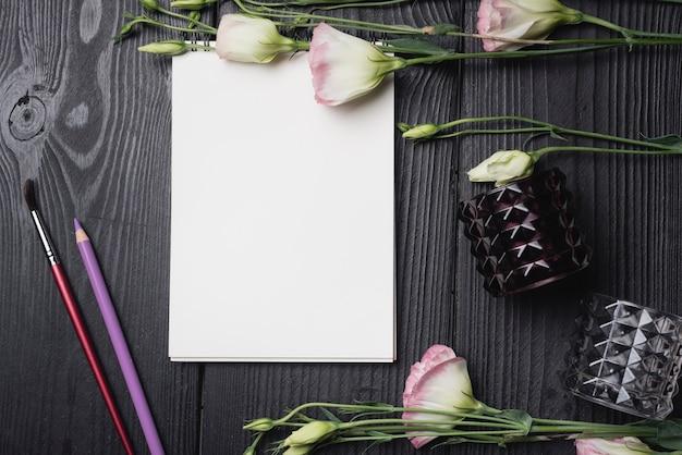 Frische blumen mit leerem weißbuch mit farbigem bleistift und bürste auf hölzernem schwarzem schreibtisch