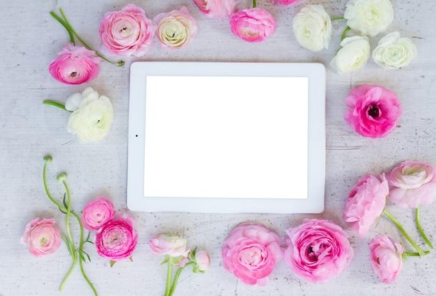 Frische blumenrahmen des rosa und weißen ranunkels mit tablette auf flacher laienszene des weißen hölzernen hintergrunds