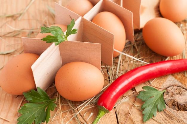 Frische braune eier, petersilie und chili