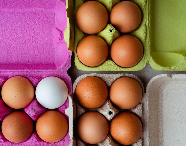 Frische braune und weiße eier in farbigen pappbehältern