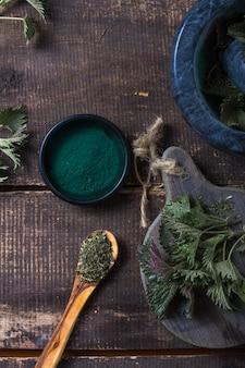 Frische brennnesselblätter auf holztisch. urtica dioica öl mit spirulina-pulver, eine gesunde ergänzung zur verbesserung der gesundheit.