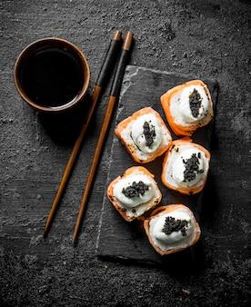 Frische brötchen mit lachs, frischkäse und kaviar. auf schwarzem rustikalem tisch