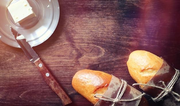 Frische brötchen zum frühstück. brötchen mit butter zu einer tasse kaffee am morgen. frühstück im hotel brötchen marmelade tee und ein blumenstrauß.
