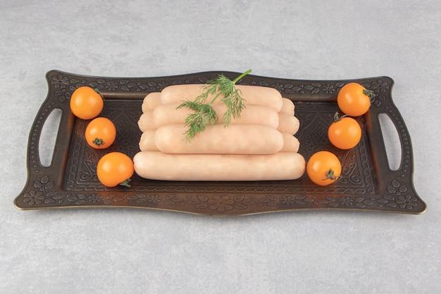 Frische brühwürste und kirschtomaten auf tablett.