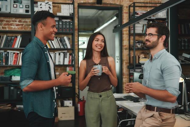 Frische büronachrichten junge lächelnde kollegen in freizeitkleidung, die tassen halten und über etwas sprechen