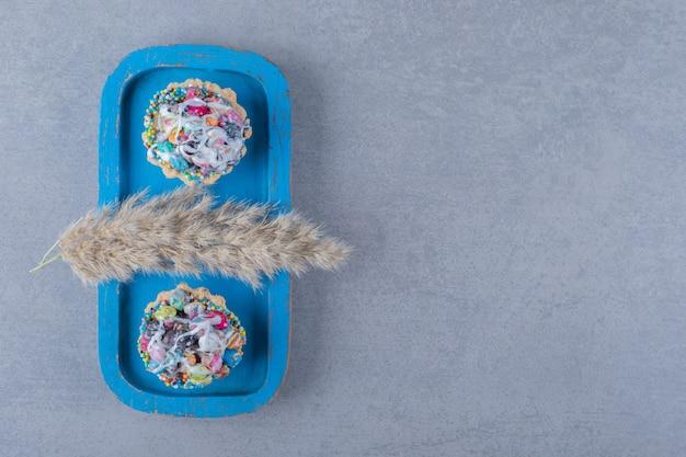 Frische bunte hausgemachte kekse auf blauem holzbrett