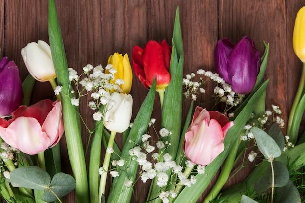 Frische bunte tulpen und atemblume des babys auf hölzernem schreibtisch