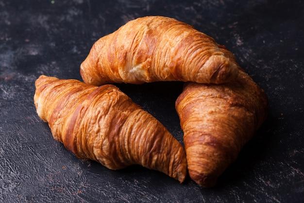 Frische buttercroissants auf dunklem holztisch. französische küche.