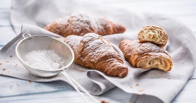 Frische buttercroissants mit zuckerpulver auf dem küchentisch bestreut.