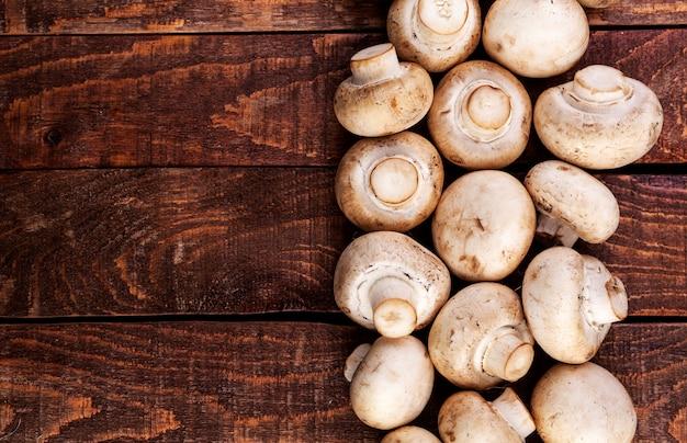 Frische champignonpilze auf holztisch, draufsicht. kopieren sie platz