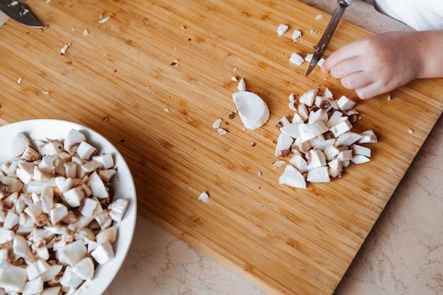Frische champignons auf einem holzbrett mädchen schneidet pilze mit einem messer